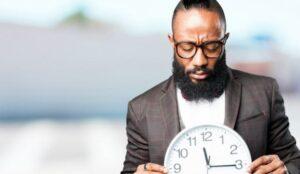 bebaarde man die naar een klok kijkt