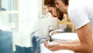 het wassen van de baard over de gootsteen