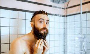 man die de baard schoonmaakt onder de douche