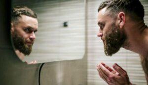 man die zijn baard schrobt